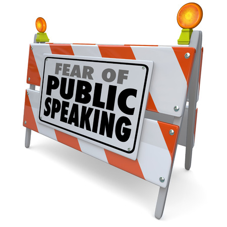 Fear of Public Speaking words on a road construction barrier or barricade illustrating anxiety or stress over delivering a speech at a big event, meeting or convention photo