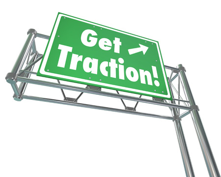 traction: Get Traction words on a green road or freeway sign illustrating the gaining of momentum or making progress with acceptance or popularity Stock Photo