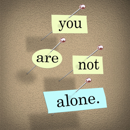 You Are Not Alone words on paper pinned to a bulletin board assuring you youre part of a community or team photo
