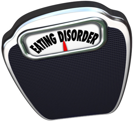 Eating Disorder words on a scale to illustrate dieting problems such as anorexia and bulimia photo