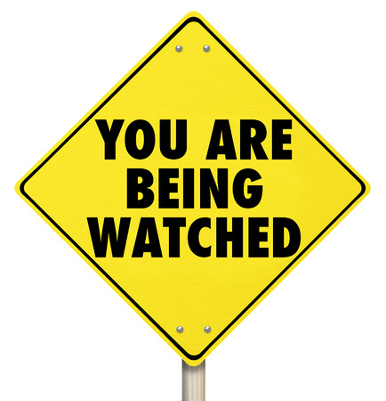 under surveillance: You Are Being Watched words on a yellow warning sign as a violation of privacy or security protection to prevent crime