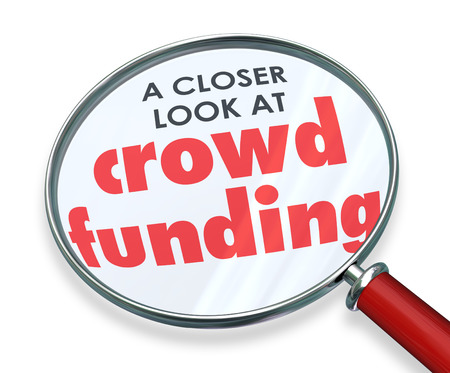 crowd source: Crowd Funding words under a magnifying glass for a closer look at investing through internet websites to fundraise campaign for your new project