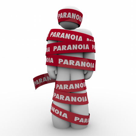 terrorized: Man wrapped in red tape with Paranoia word as someone who is worried, anxious, stressed out or afraid of fears