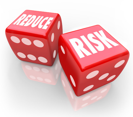 risky behavior: Reduce Risk words on two red dice to illustrate lowering your chances for liability, danger, hazard or exposure while increasing safety and security
