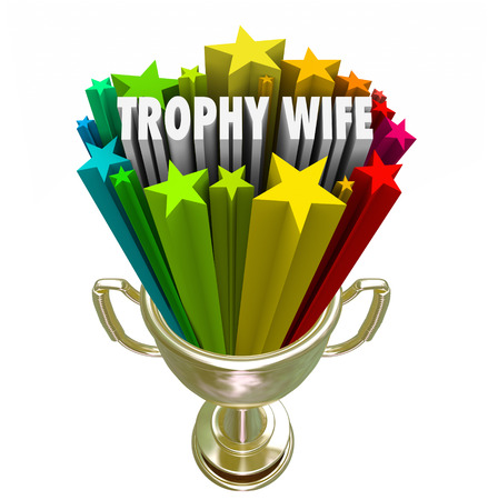 spousal: Trophy Wife 3d words in a golden trophy to illustrate the marriage of a young attractive woman to an older wealthy man or husband Stock Photo