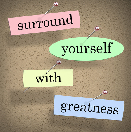 surrounding: Surround Yourself with Greatness words in a saying or quote pinned to a bulletin board for motivation and inspiration Stock Photo