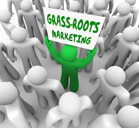 grass roots: A man holding a Grass Roots Marketing sign in a crowd to illustrate local advertising and spreading word of mouth to promote your product or service Stock Photo