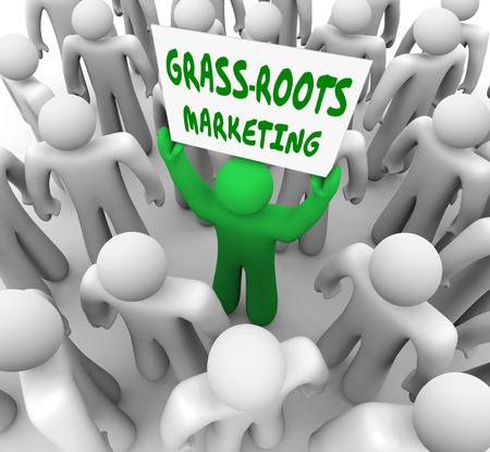 promover: Um homem segurando um sinal Ra�zes de Marketing da grama em uma multid�o para ilustrar a publicidade local e espalhando a palavra da boca para promover o seu produto ou servi�o