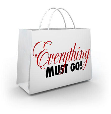 go out: Everything Must Go words on a white shopping bag at a store holding a Going Out of Business sale to clear out its inventory Stock Photo