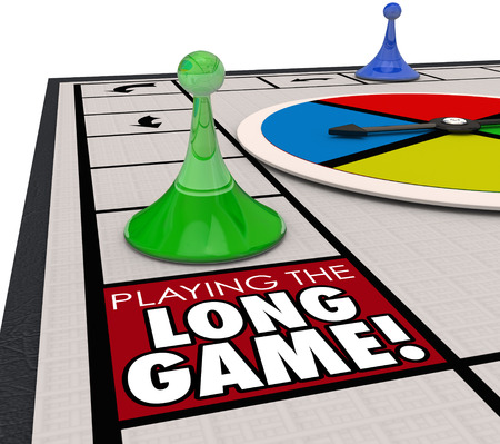 A player moving a game piece around the board to land on a square marked Playing the Long Game to illustrate investing for the long term future for better returns and winning in life Stock Photo