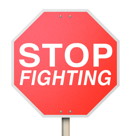 disputed: Stop Fighting words on a red road or traffic sign telling you to negotiate with your enemy to reach a truce or ceasefire and end the violence
