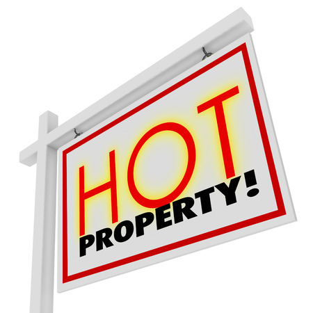 demanded: Hot Property words in sizzling red letters on a white home or house for sale real estate sign to illustrate a popular or in-demand building
