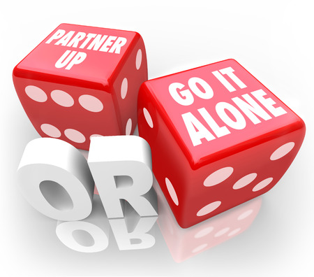 Partner Up or Go It Alone words on two red dice to illustrate the choice or decision to join a group or be independent
