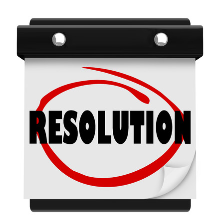 promised: Resolution word on a calendar page to illustrate a new years vow or promise to ahcieve a goal or complete a task or mission and improve your life, job or career