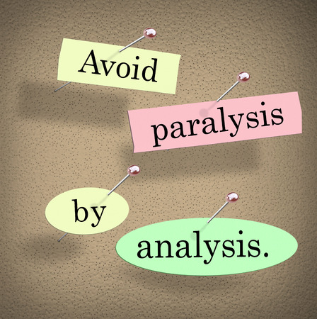 indecision: Avoid Paralysis by Analysis words in cut out papers pinned to a bulletin board as a saying or quote warning you not to overthink or be undecided by endless committee discussion