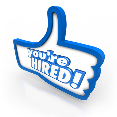 hired: Youre Hired words in 3d letters on a thumbs up symbol to illustrate the best or top job candidate being hired for an open position