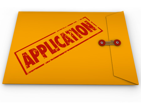 Application word stamped in red ink on a yellow envelope containing forms, paperwork or a resume to submit to an employer or applying for a bank loan or credit Stock Photo