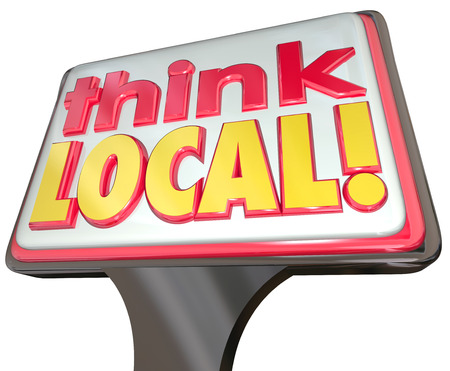 supporting: Think Local words on a sign advertising community stores or business for buying from neighborhood merchants or sellers and supporting your nearby companies