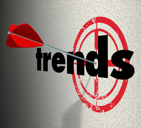 Trends word on a wall with bulls-eye and arrow hitting the target to illustrate fads or current popular products Stock Photo