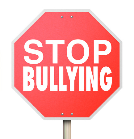 Stop Bulling words on a red road or street sign to prevent children from picking on, fighting or being mean to other kids Stock Photo
