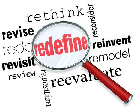 Magnifying glass on the word Redefine and related terms such as revise, redo, revisit, review, reposition, rethink, reconsider, reinvent, remodel and reevaluate Stock Photo