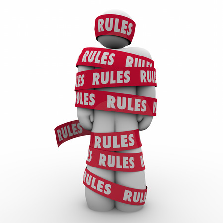 law breaking: Rules word on red tape wrapped around a man or person to illustrate following regulations, guidance or laws to be in compliance Stock Photo