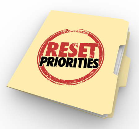 precedence: Reset Priorities words stamped on a manila folder to illustrate a change in the most important jobs or tasks to handle first in order