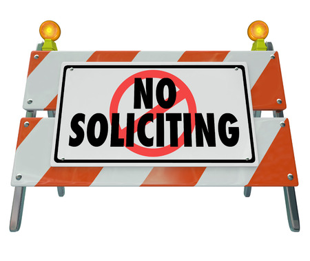 unsolicited: No Soliciting words on a barrier, blockade or sign to illustrate blocking annoying salespeople from selling to and annoying you