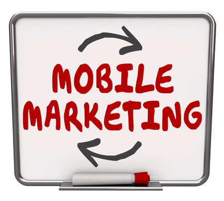 Mobile Marketing words written on a dry erase board to illustrate modern company strategy to sell to customers via apps on mobility devices such as smart or cell phones and tablets photo
