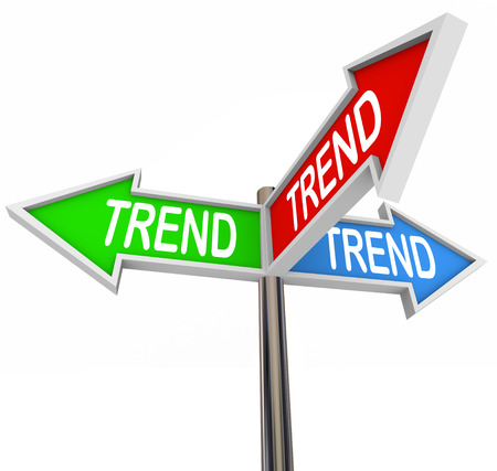 Trend word on three arrow signs pointing you in the direction of hot or new trending topics, products or news Foto de archivo