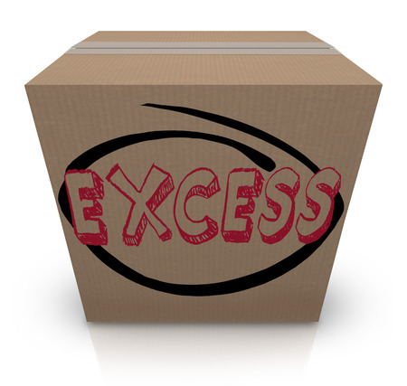surplus: Excess word written on a cardboard box to illustrate too much supply, extra inventory or overstock of goods or merchandise at a store, storage facility or warehouse