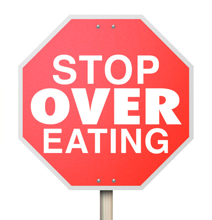 consume: Stop Over Eating words on a red road sign as warning to reduce food intake, pay attention to good nutrition and consume smaller portion sizes