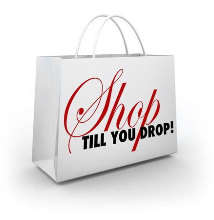 Comprar hasta el cansancio palabras en una bolsa de la compra en blanco para ilustrar descuentos y ventas para animarle a gastar más dinero Foto de archivo - 40336362