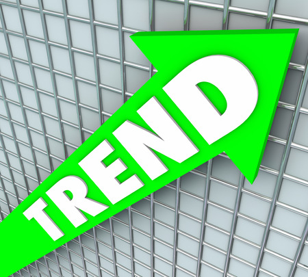 business trending: Trend word on a green arrow on chart or graph to illustrate rise, improvement, increase, higher popularity or good results