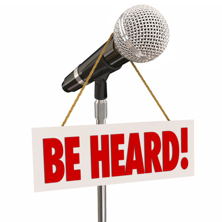 heard: Be Heard words on a sign hanging on a microphone to illustrate sharing an opinion or viewpoint through public speaking in an open forum Stock Photo