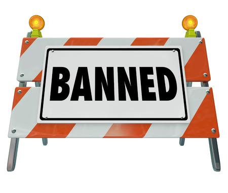 punished: Banned word on a barricade or road construction warning sign to illustrate something that is forbidden, illegal, censored or prohibited Stock Photo