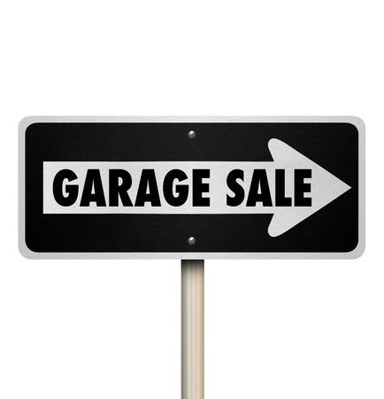 sale sign: Garage Sale road sign pointing way or direction to a rummage, moving, lawn or resale event in a community or neighborhood Stock Photo