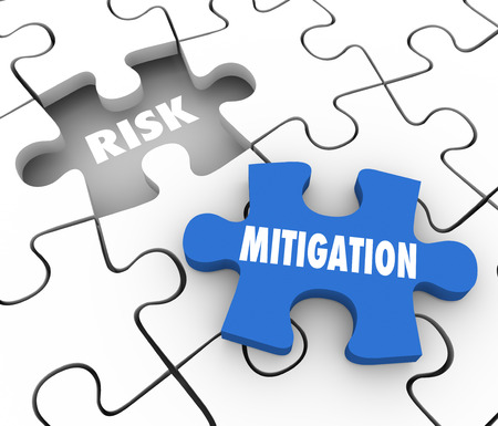 Risk Mitigation words on puzzle pieces to illustrate reducing problems, trouble, dangers or hazards and increase security and protection from harm Foto de archivo