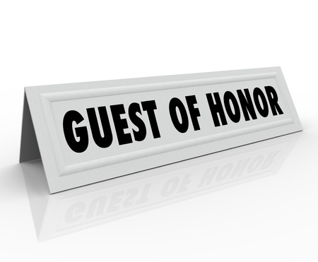 honour: Guest of Honor words on a name tent card or placeholder reserving a seat for a dignitary or to welcome a keynote speaker Stock Photo