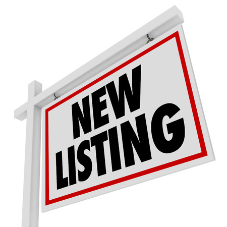New Listing words on a home or house for sale real estate sign at a new building or property just added to the market for buyers and sellers to view 写真素材