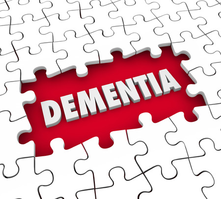 brain aging: Dementia word in a hole with puzzle pieces to illustrate aging, memory loss, mind or brain degeneration and medical treatment for the condition Stock Photo