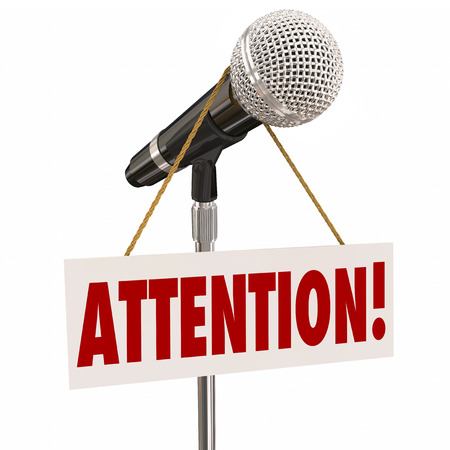 urging: Attention word on a hnaging sign over a microphone urging you to listen or hear an important announcement, news or speech