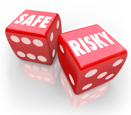 mitigate: Risky Vs Safe words on dice to illustrate reduction in liability and mitigate loss or accidents Stock Photo