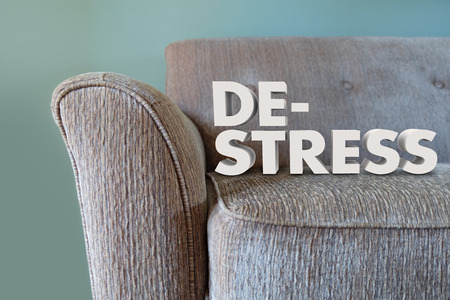 destress: De-Stress words in 3d letters on a couch to illustrate unwiding mind, body and soul to relax Stock Photo