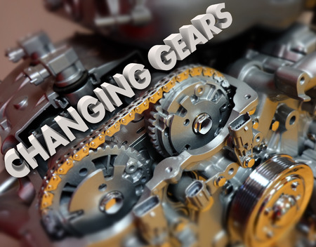 slower: Changing Gears in 3d letters on a car, auto or vehicle engine to illustrate shifting a topic or increasing speed Stock Photo