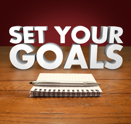 envisioning: Seet Your Goals words in 3d letters above a notepad and pen for you to write missions, objectives or wishes in a list