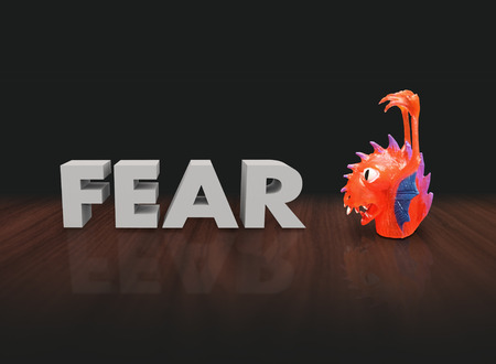 fear: Fear word in 3d white letters beside a red plastic finger puppet monster