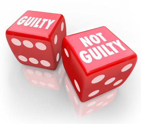 legal: Guilty or Not Guilty words on two red dice to illustrate being convicted or acquitted in a court of law in judgment from a jury or judge in trial Stock Photo