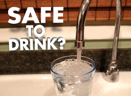 Safe to Drink question in 3d words beside a faucet pouring water in a glass