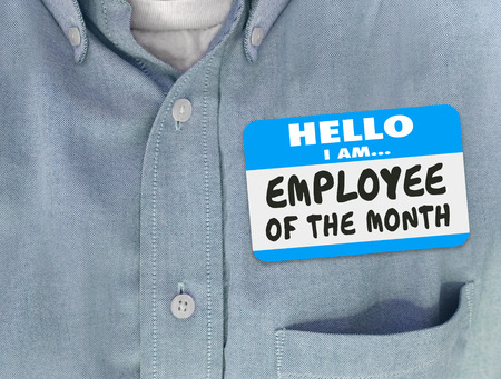Employee of the Month words written on a nametag worn by a worker or top staff member in a blue shirt Foto de archivo